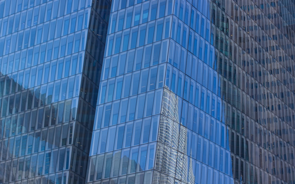 low-angle photography of blue glass walled high-rise building