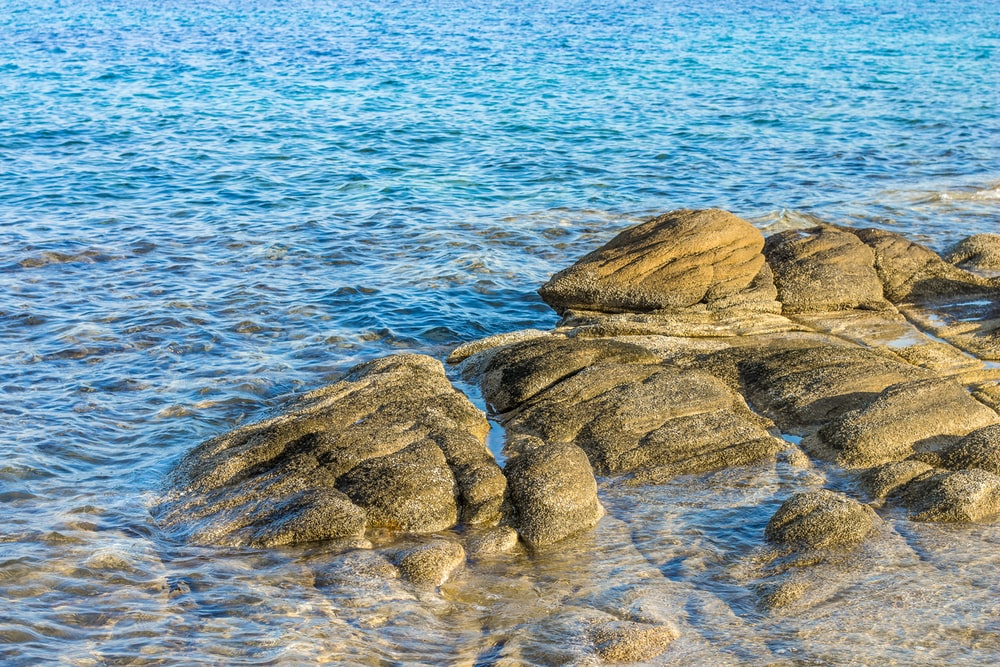 brown rock formations on blue body of water