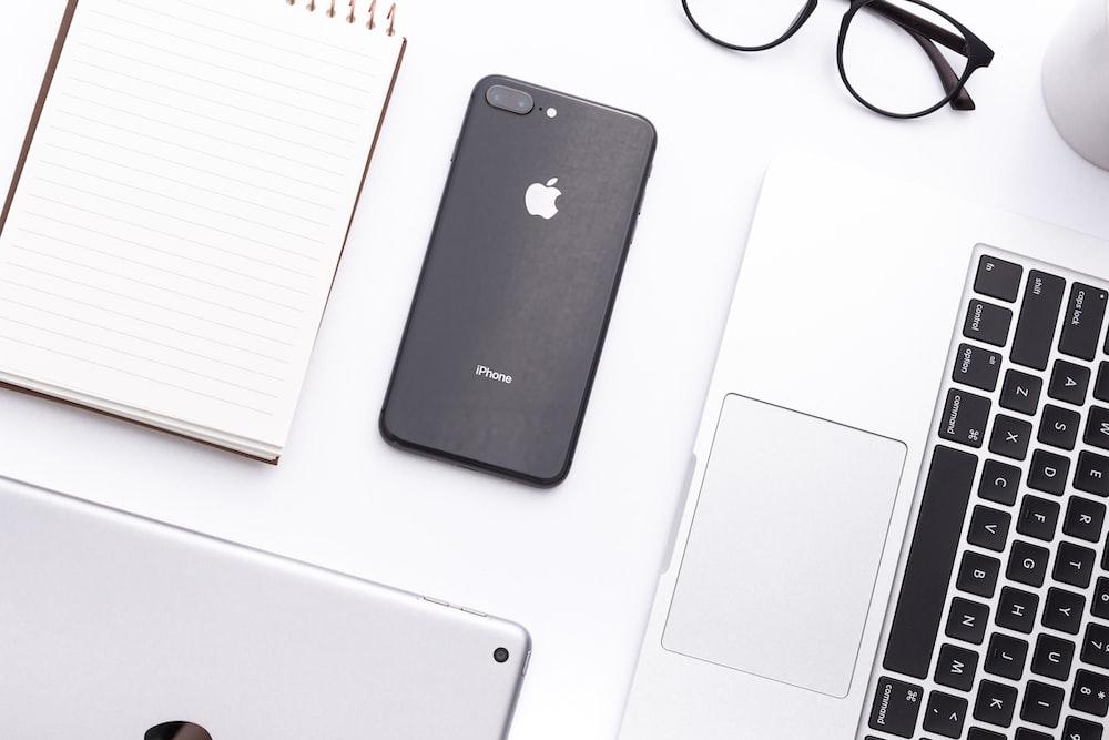 space gray iPhone X beside MacBook