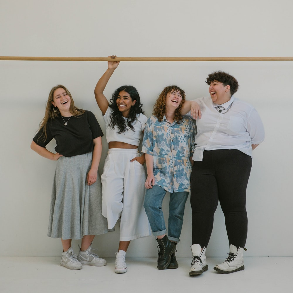 four person standing beside wall