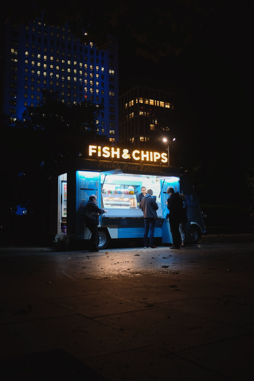 group of people standing on Fish & Chips store