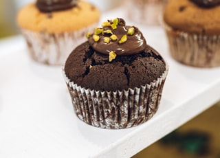 chocolate cupcake with yellow icing on white ceramic plate