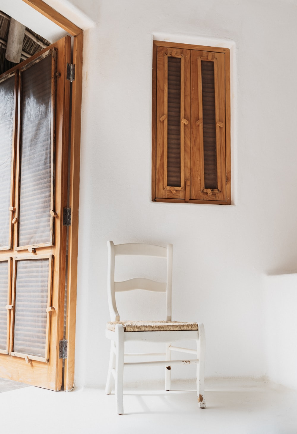 white wooden chair beside wall