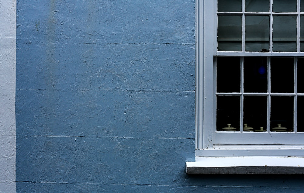 closed white window with gray wall