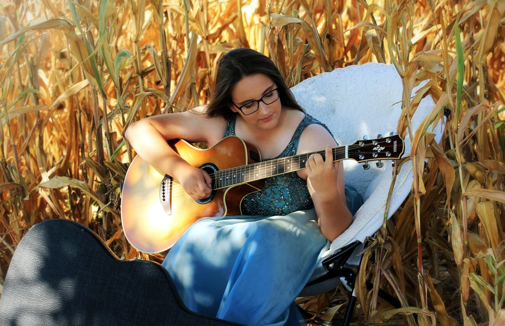 Wondrous Woman Playing Guitar Sitting On White Chair On Corn Field Caraccident5 Cool Chair Designs And Ideas Caraccident5Info