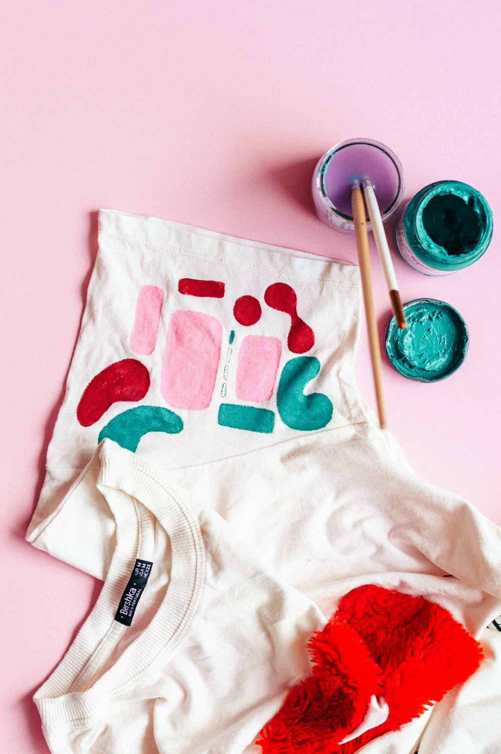 white and red crew-neck shirt beside paint with brushes