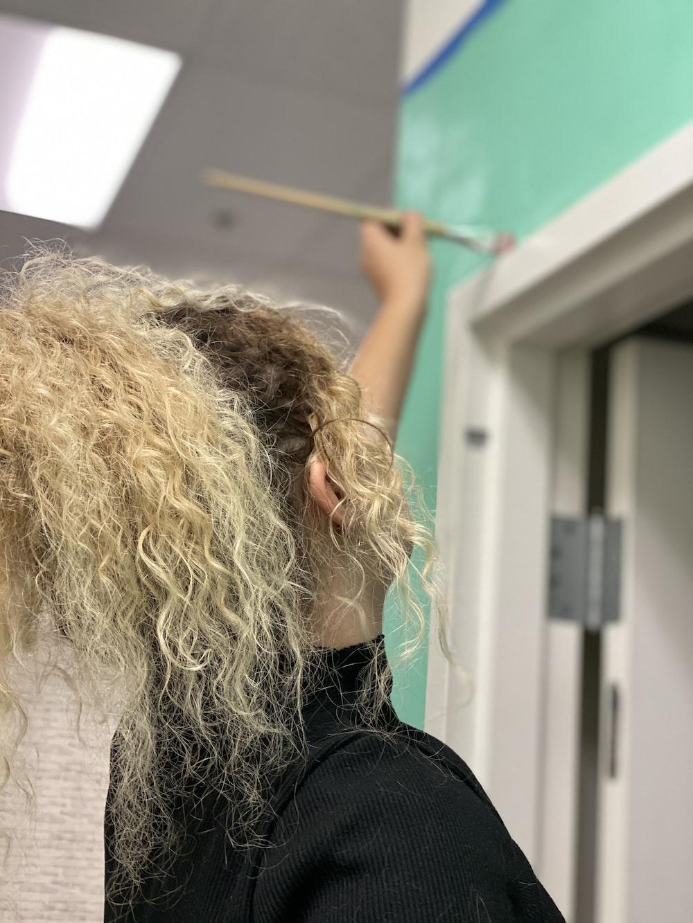 woman painting door frame