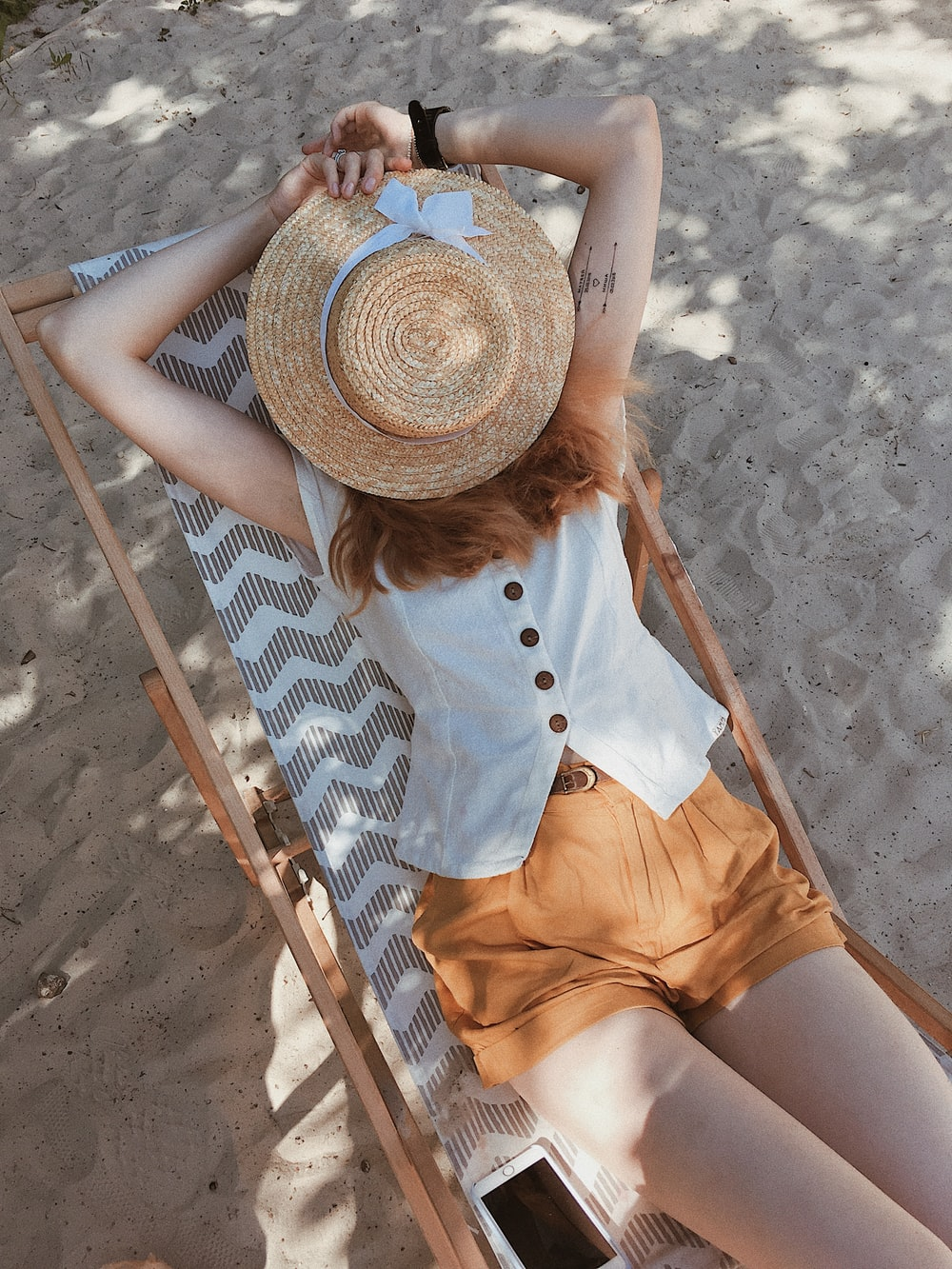 woman in white top lying on chair