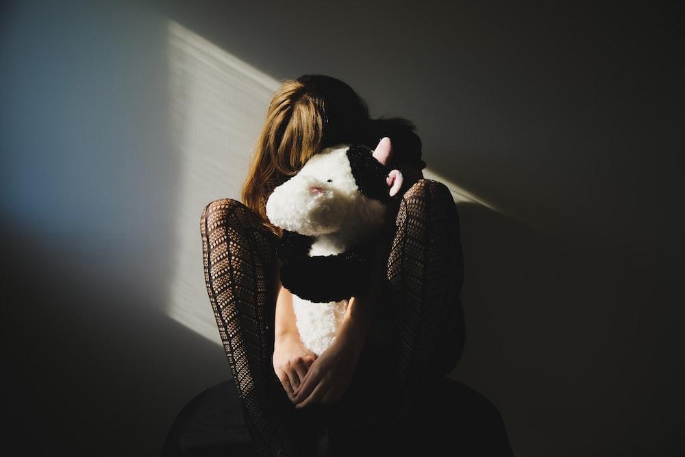 woman holding white and black animal plush toy