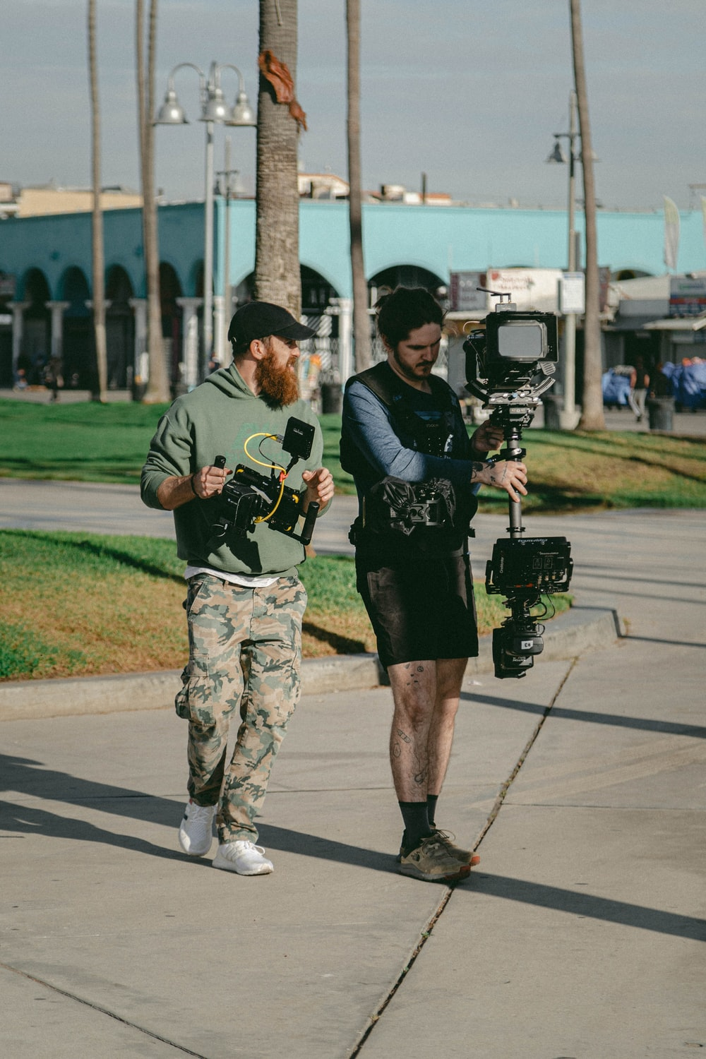 two men carrying filming camera