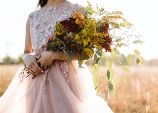 woman in pink and silver sleeveless dress holding bouquet of flowers