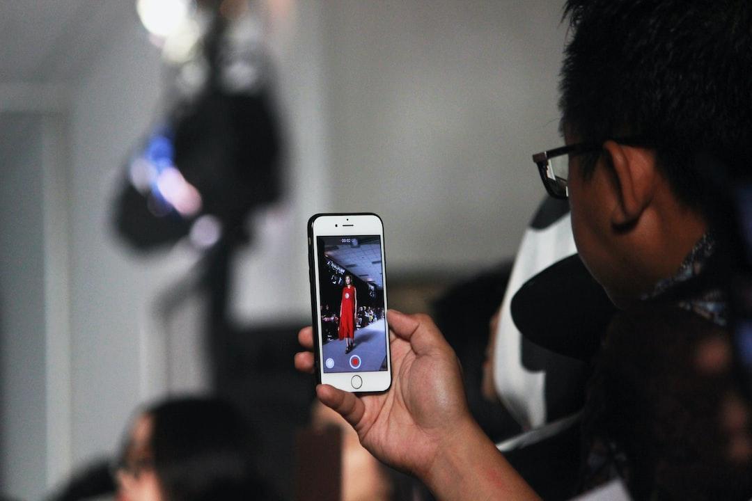 A man recording fashion show.