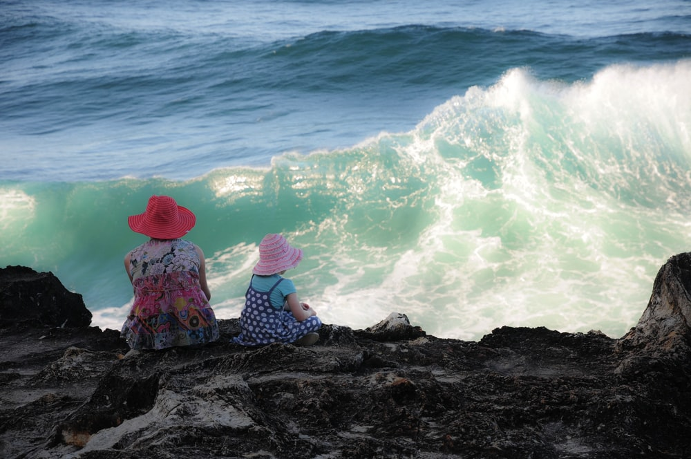 woman and girl sitting on cliff overlooking sea