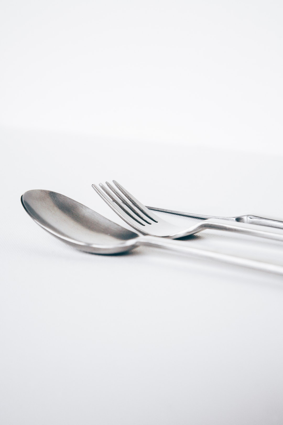 White restaurant table with silver modern styled spoon, fork and knife