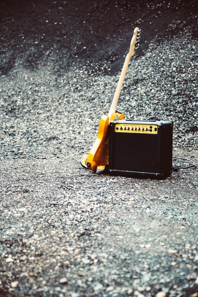 Outdoor live music set at gravel pit with guitar and portable electronic amplifier