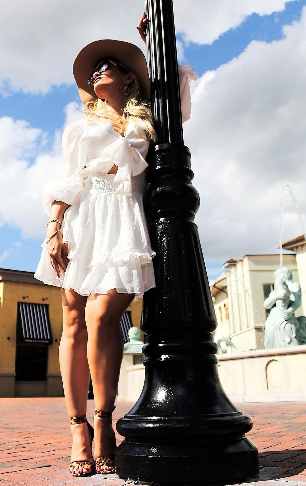 woman wearing white long-sleeved dress beside black post