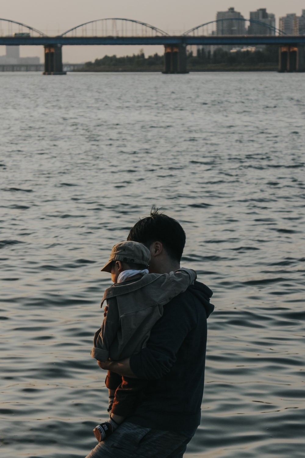 man carrying a baby in the beach