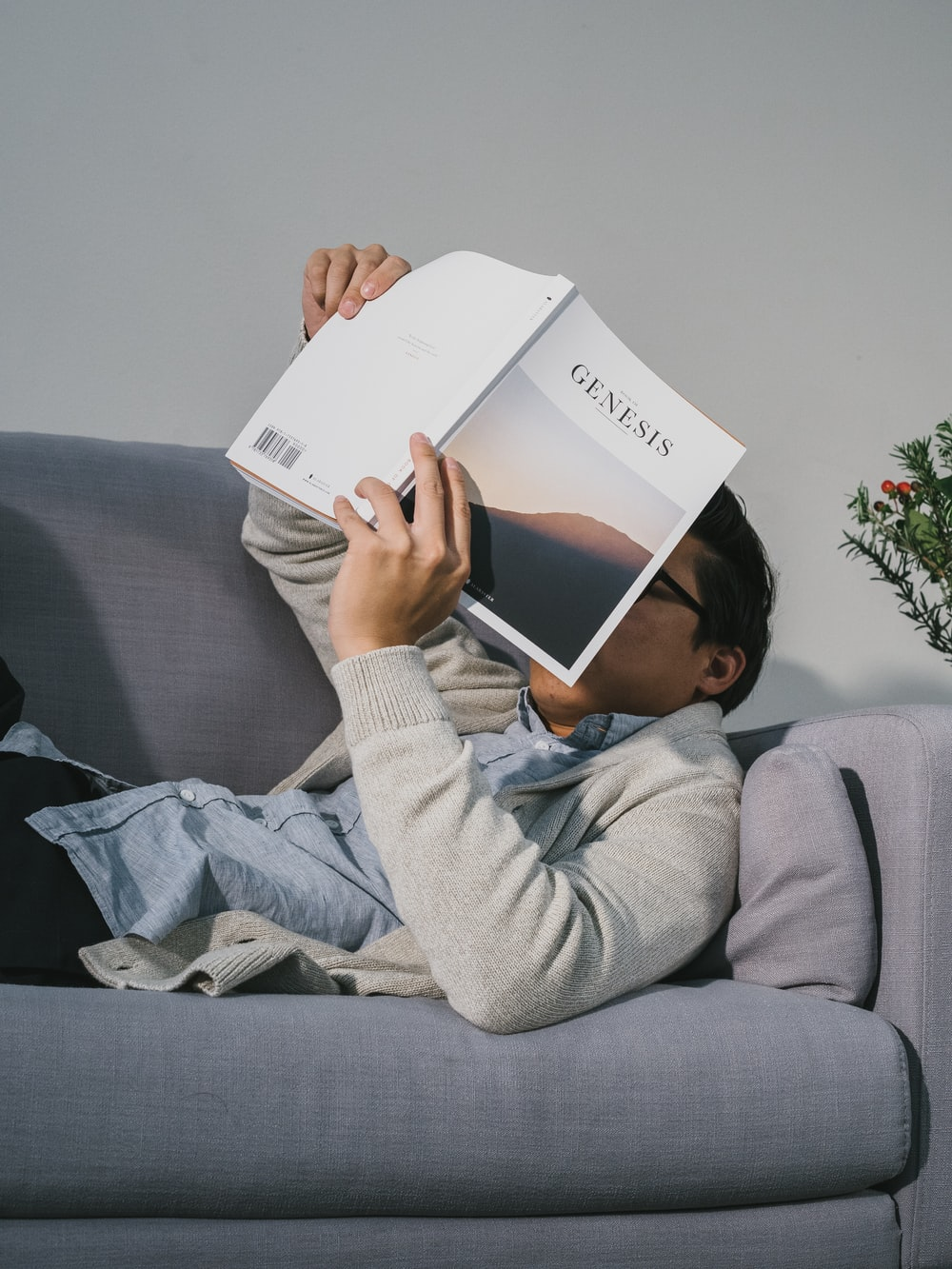 man reading book while lying on gray fabric sofa