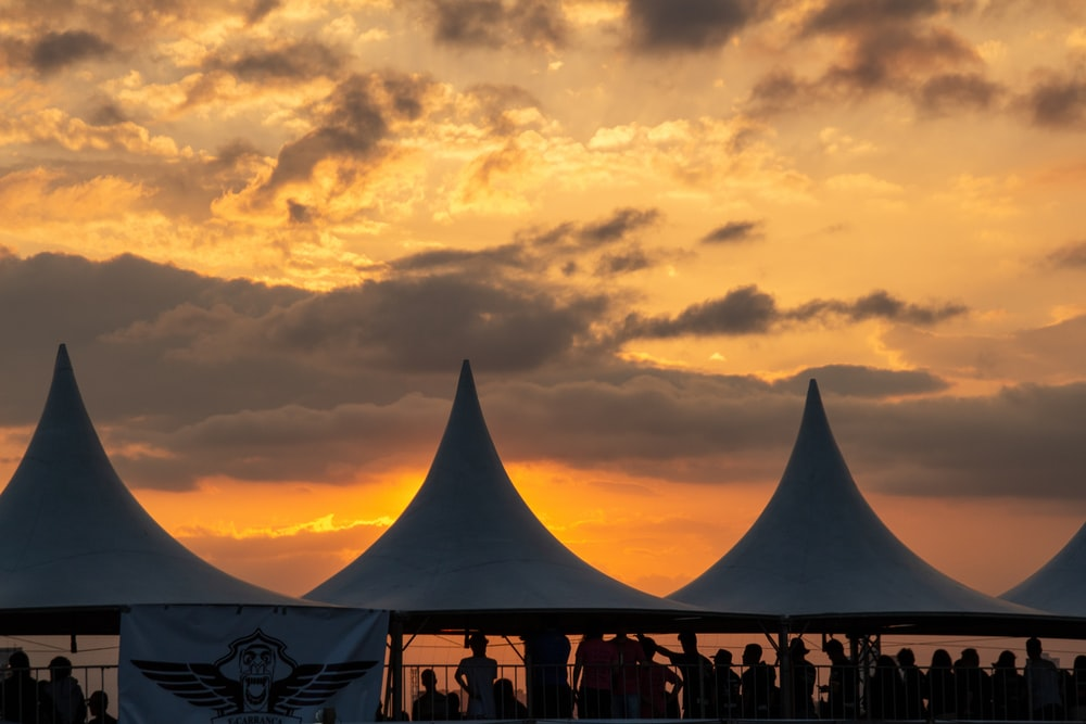 silhouette of people under tent during golden hour