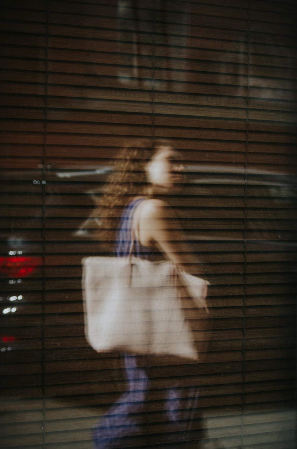 woman walking near glass wall