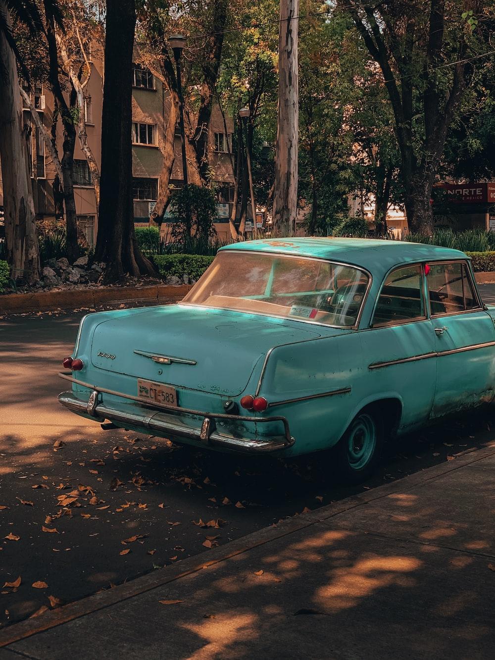 parked teal sedan beside curb