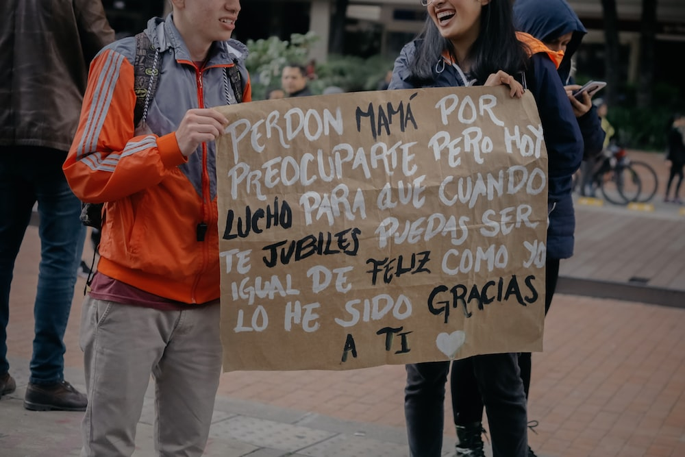 man and woman holding brown banner