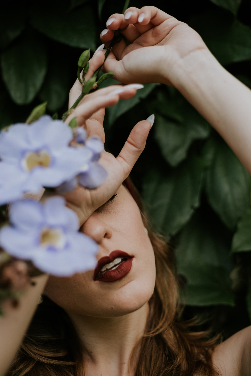 woman wearing red lipstick covered by blue petaled flower