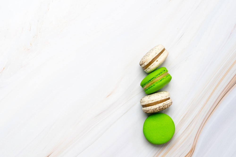 two green and two brown macarons