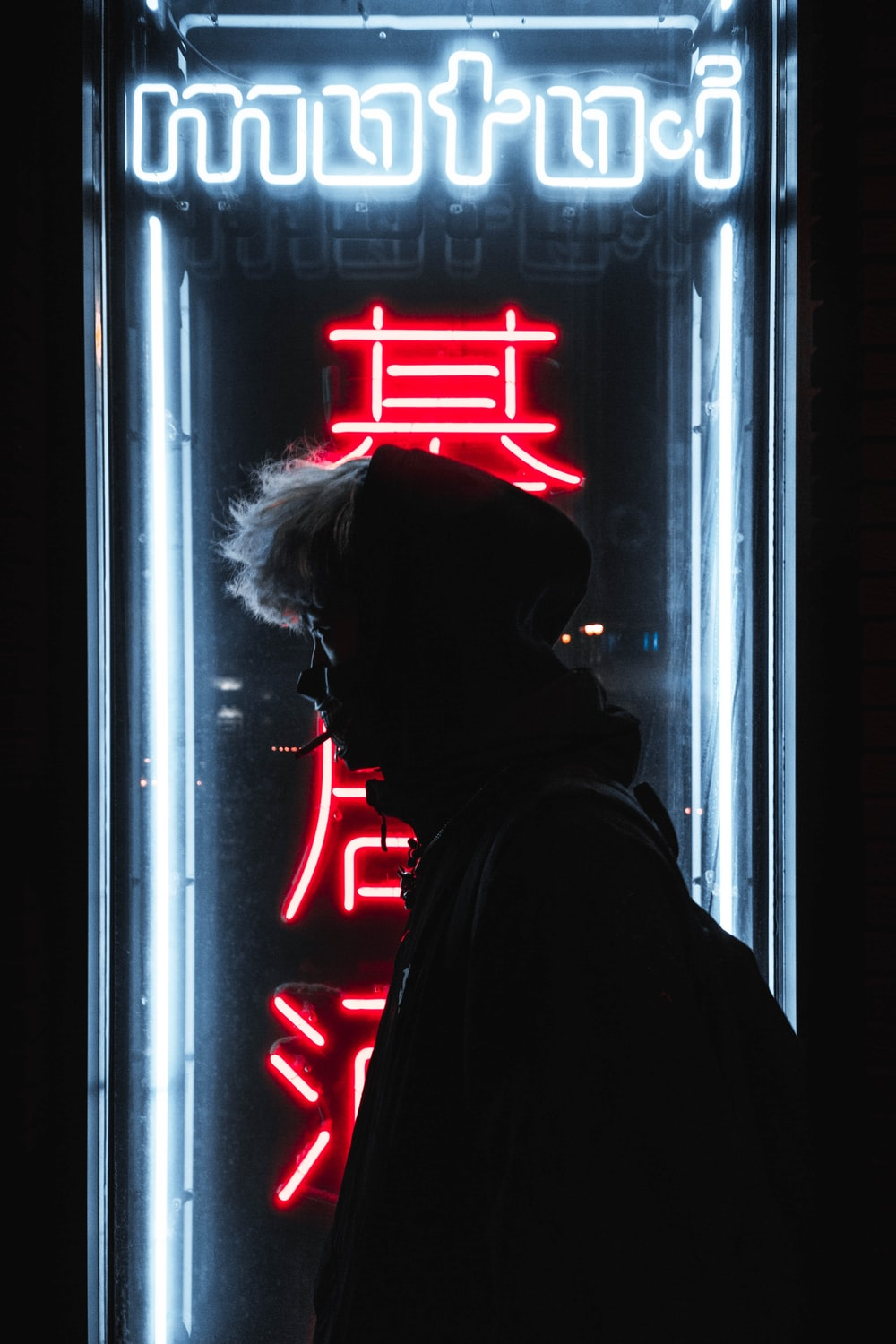 silhouette of person standing in front of neon sign