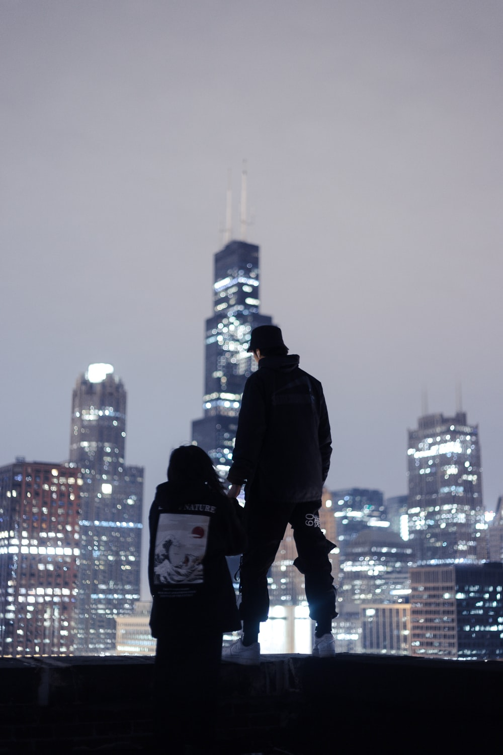 silhouette photography of two person standing near edge overlooking high-rise buildings