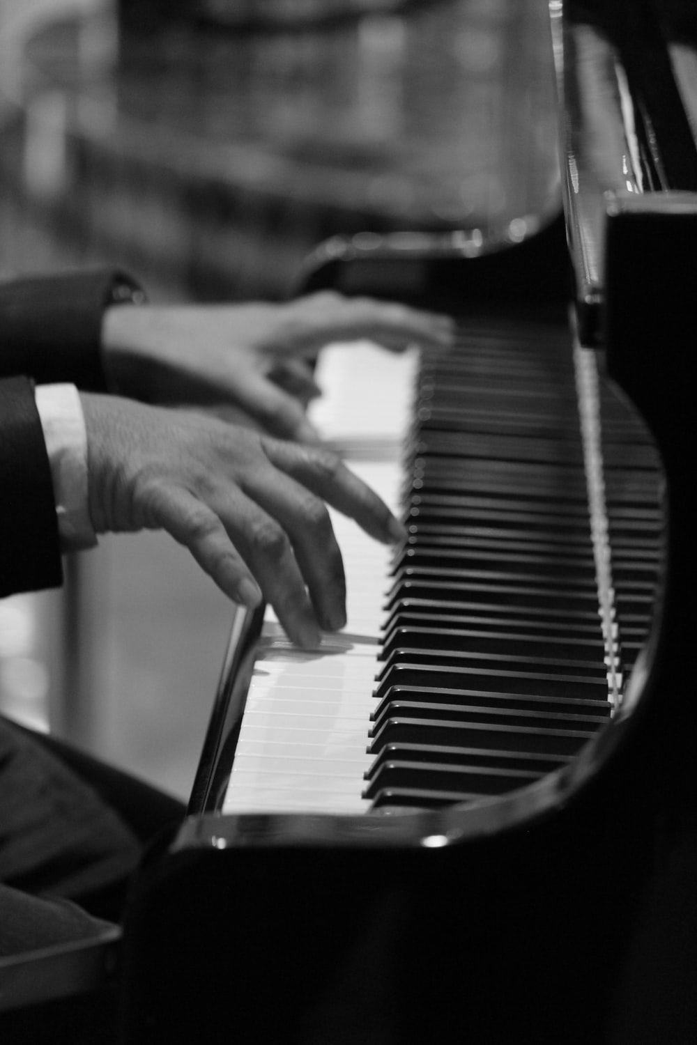 grayscale and selective focus photo of person playing piano