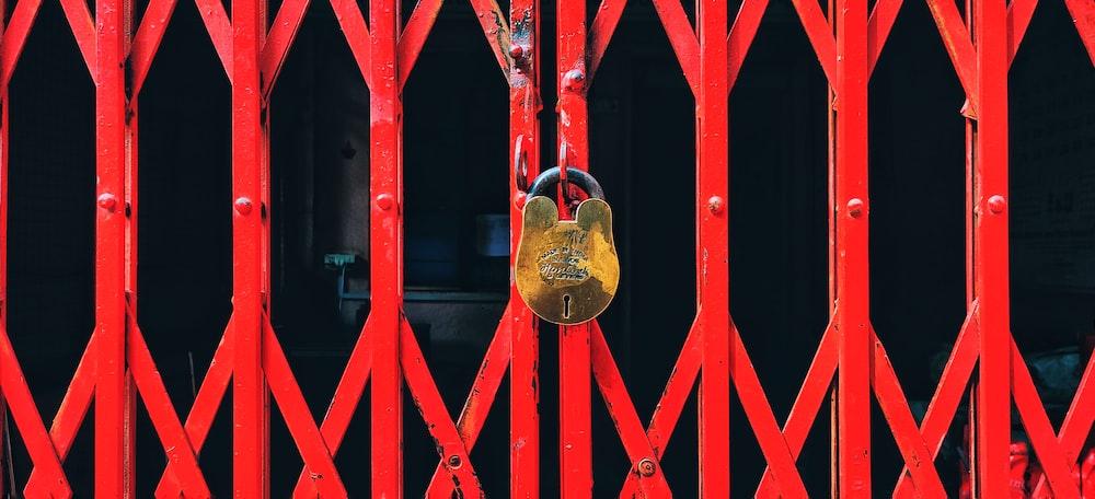 gold padlock on red gate