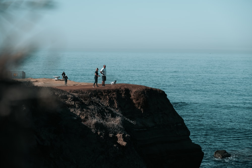 people on cliff during daytime