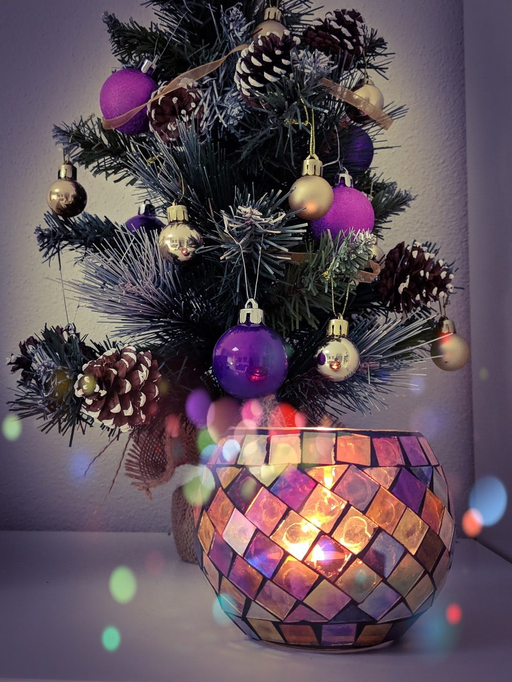 shallow focus photo of green holiday tree with purple baubles
