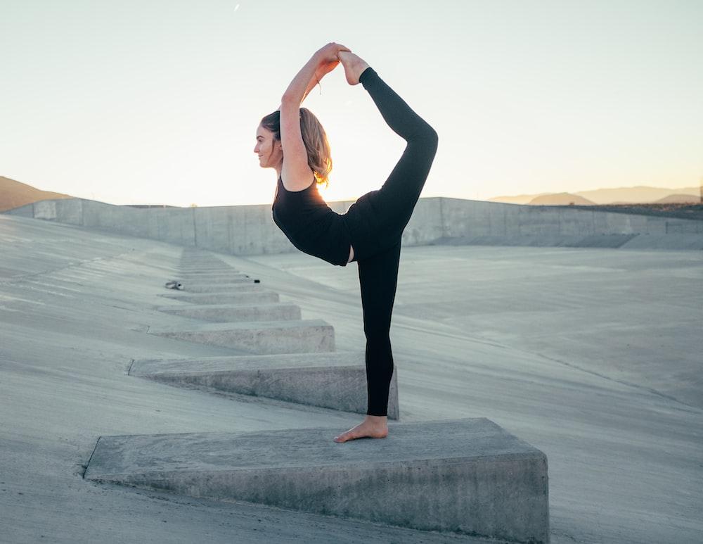 shallow focus photo of woman in black sleeveless shirt doing yoga