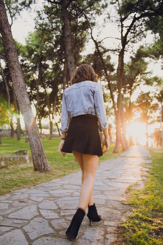 woman in blue denim jacket walking on concrete pathway