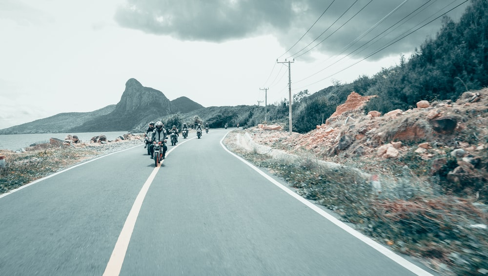 group of people riding motorcycle on road