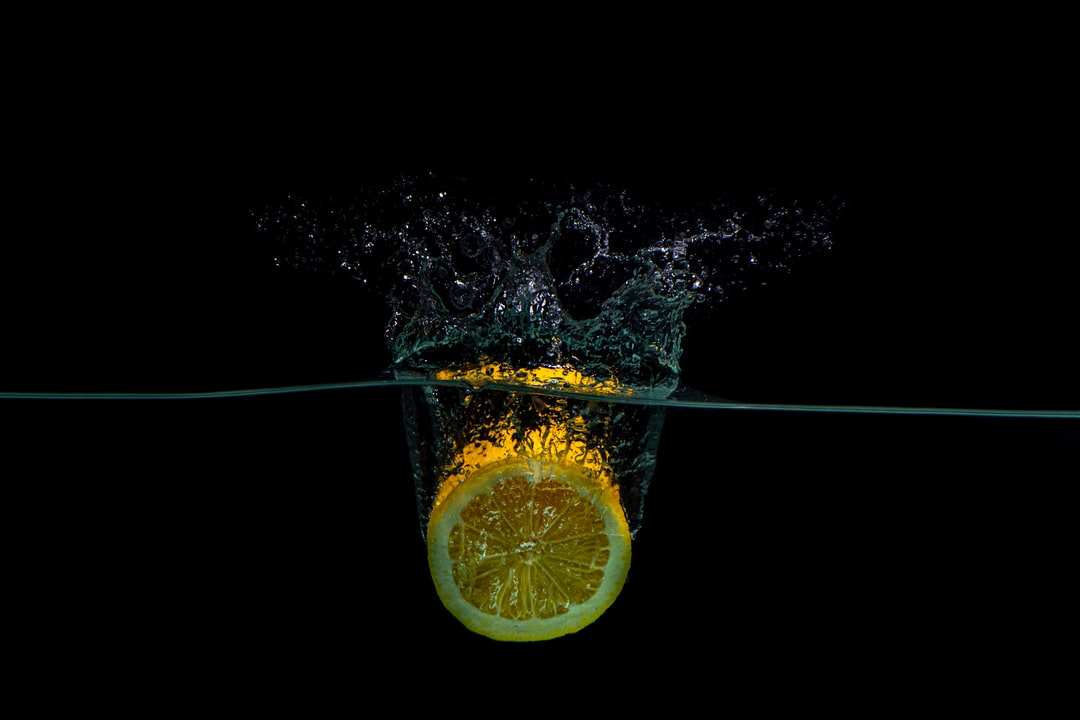 half of a lemon dropping into water against a black background. Splash fruit photography.