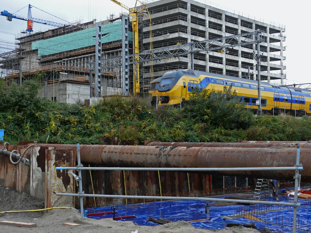 yellow and blue train passing by gray building