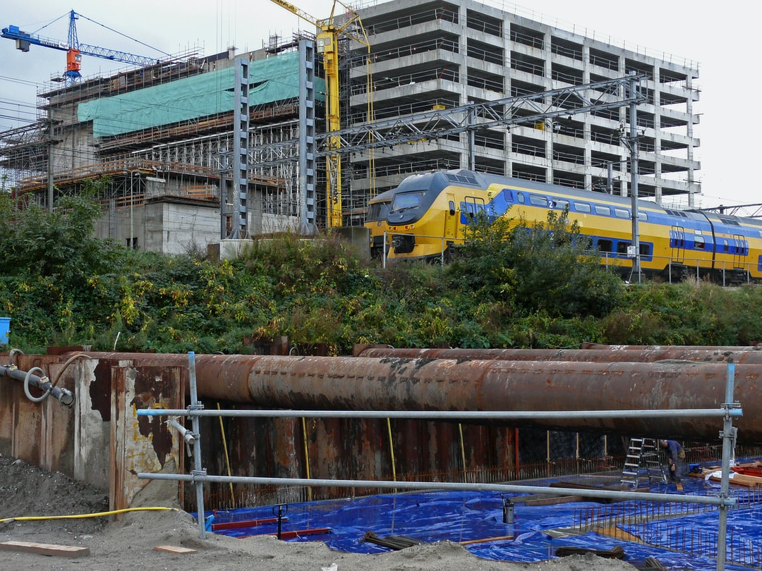 Picture of construction-works along the traintrack in Amsterdam city. Above the new arising building of the municipal library O.B.A. at the Oosterdokseiland. At the bottom a building pit with rusty sheet piling; free urban photo, made in October, 2006 - photographer, Fons Heijnsbroek.