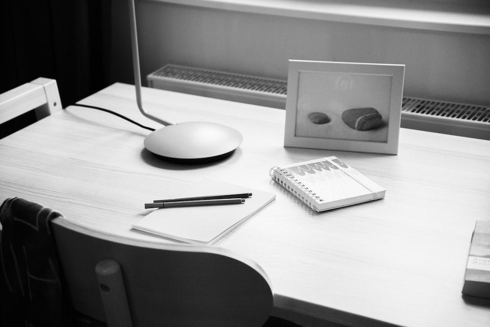 notebook on desk near photo frame