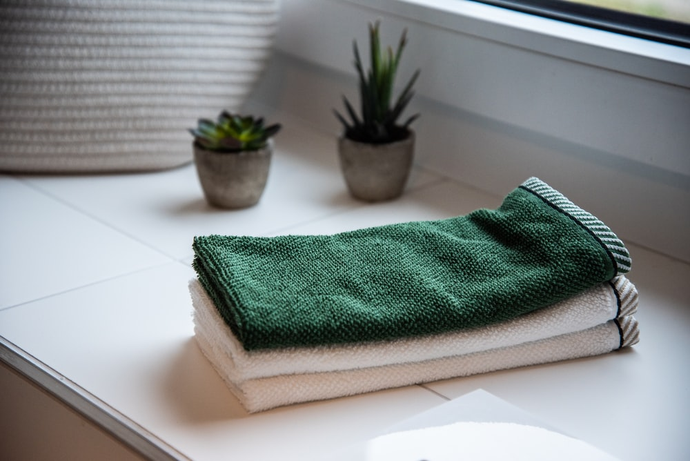 folded towels near potted plants