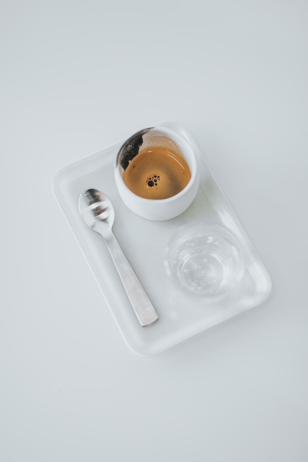 white cup with spoon with bowl and tray