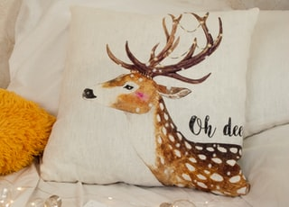 brown and white deer printed throw pillow