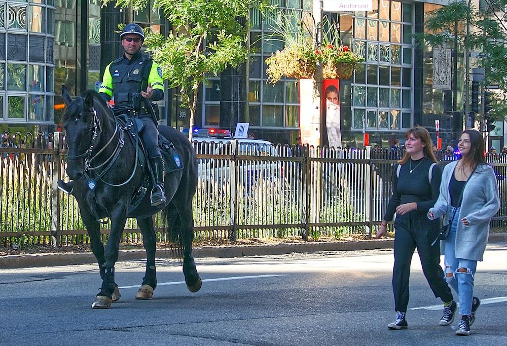 policeman riding horse beside two walking women