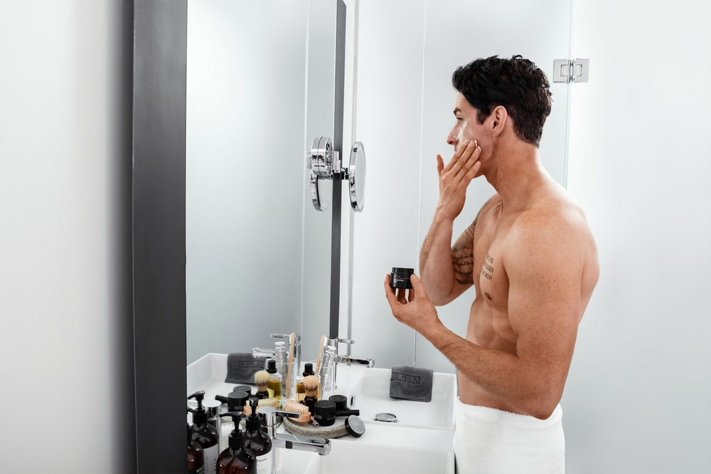 topless man standing beside sink