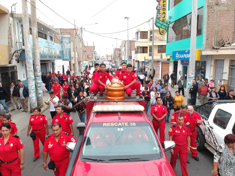 coffin on red truck beside men in red uniform