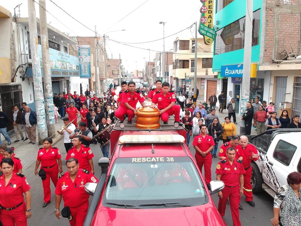 coffin on red truck beside men in red uniform