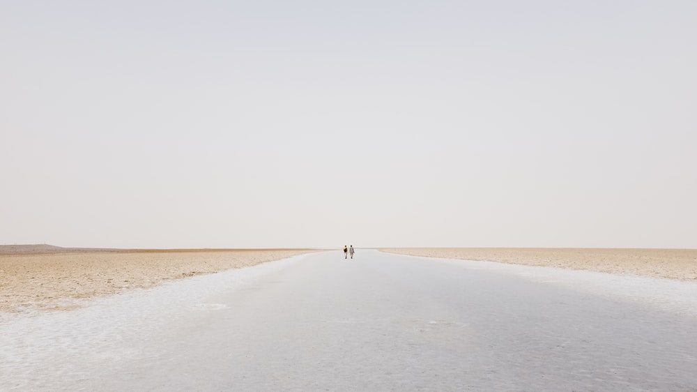 two person walling on desert