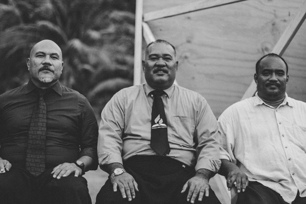 gray-scale photo of 3 man sitting on chair